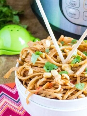 bowl of peanut Thai noodles with chopsticks in it
