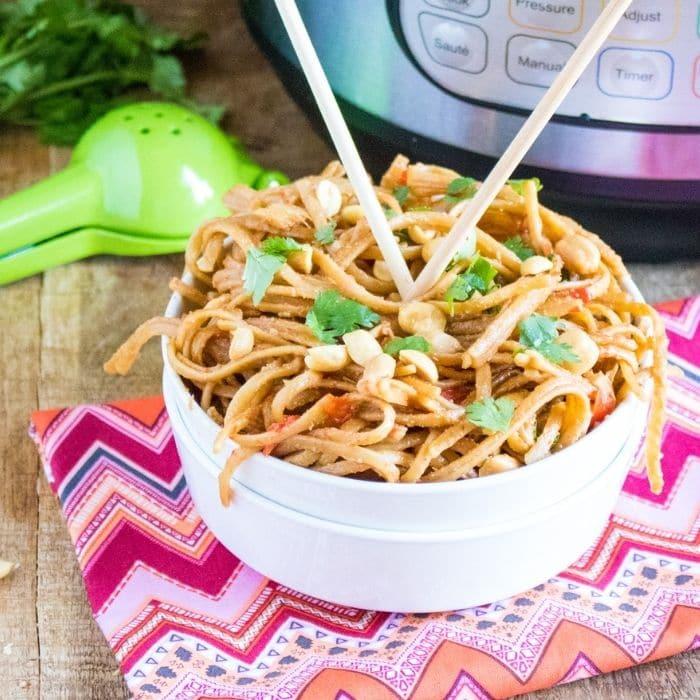 peanut chicken pasta in a white bowl with chopsticks in it