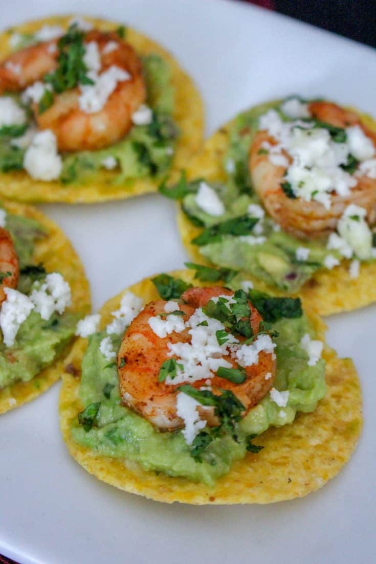 Mexican shrimp guacamole bites are perfectly salted tortilla chips topped with guacamole, seasoned shrimp, and crumbles of Queso Fresco cheese. | #appetizer #gamedayfood #shrimp #seafood #chips #mexican #fresco #guacamole #bitesize