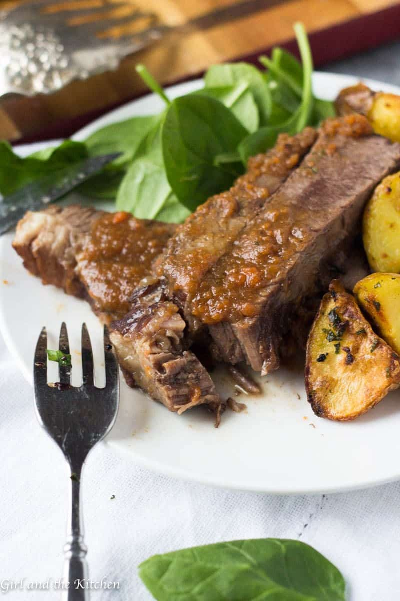 braised beef ribs in instant pot on a plate with salad and potatoes