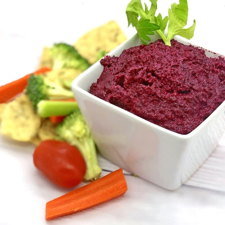 beet dip with veggies around it