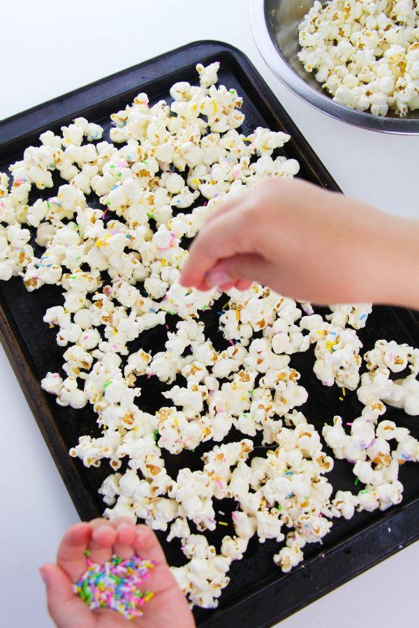 sprinkling sprinkles onto popcorn