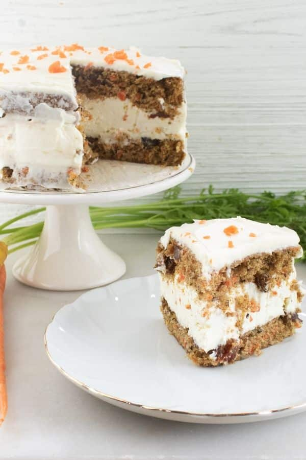 layered carrot cake on a plate with whole cake behind it