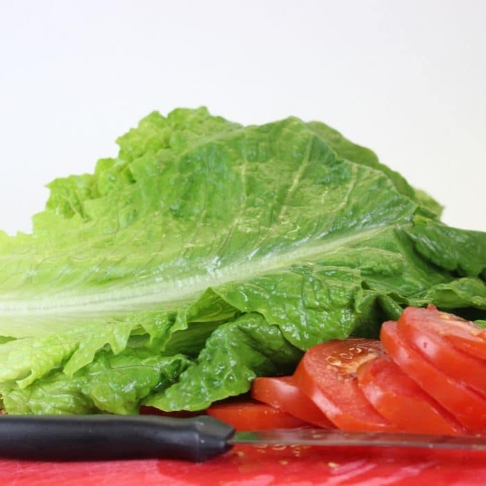 lettuce and tomatoes on cutting boards