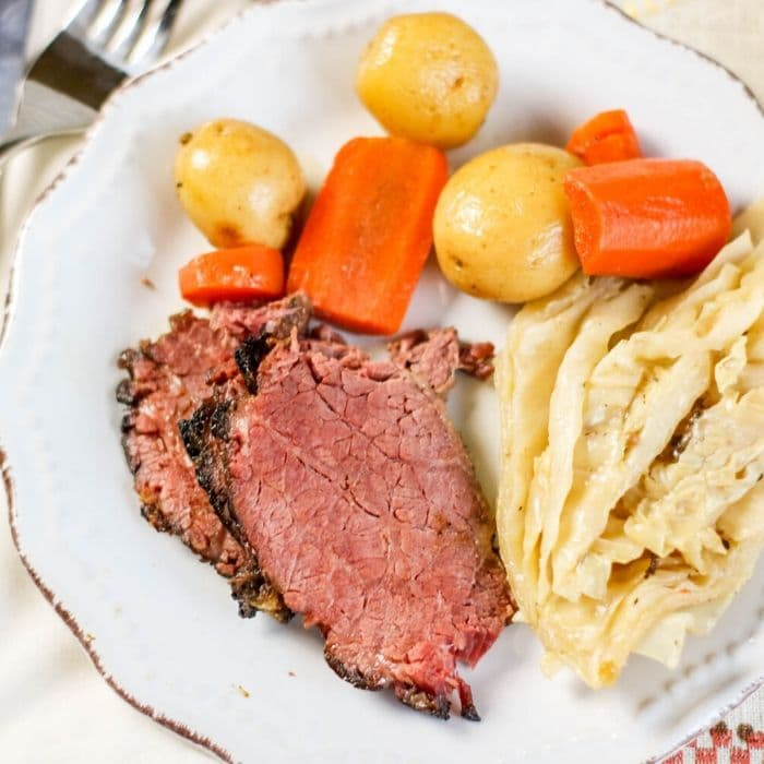 corned beef on a plate with cabbage and vegetables