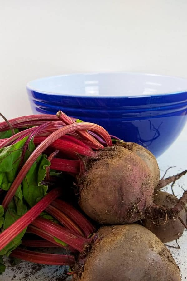 beets on counter with blue bowl behind it