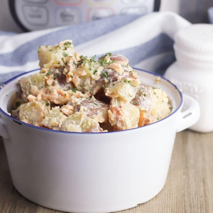 cheddar potato salad in a white and blue bowl