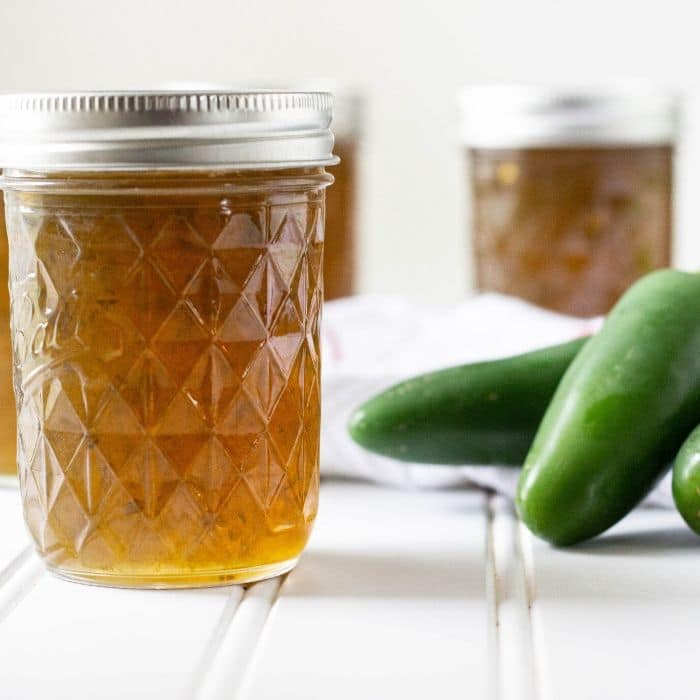 jalapeno pepper jelly in a jar with fresh jalapeno peppers