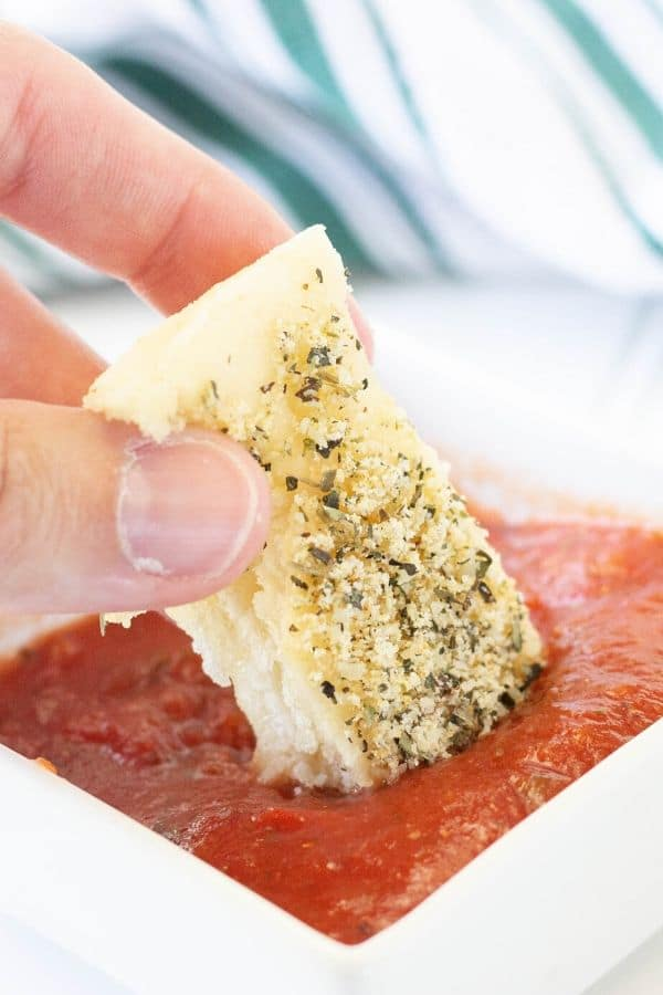 breadstick being dipped into a marinara sauce
