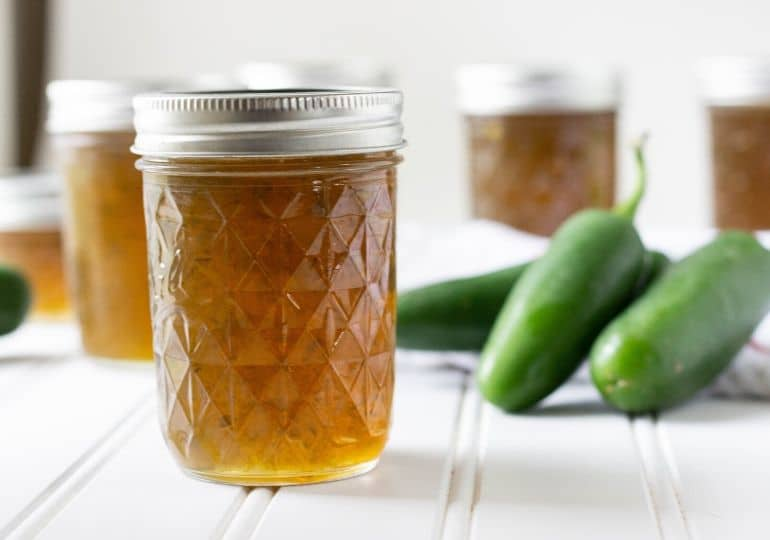jalapeno jelly with fresh jalapenos by it