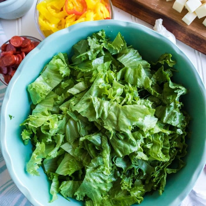 bowl of lettuce with other salad ingredients around it