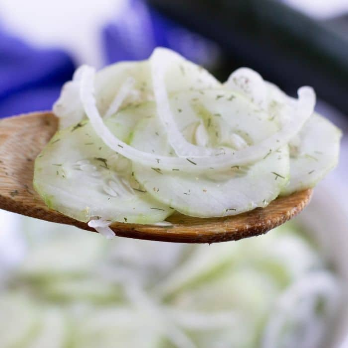 cucumber vinegar salad on a wooden spoon