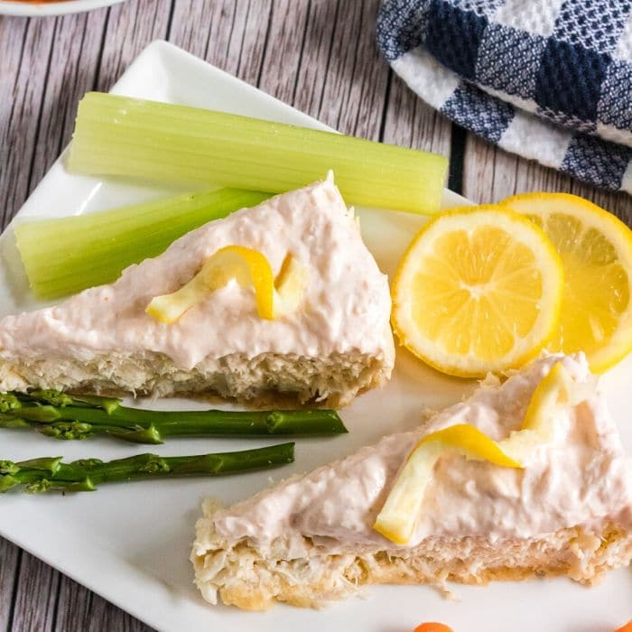 slices of crab cheesecake on platter with vegetables