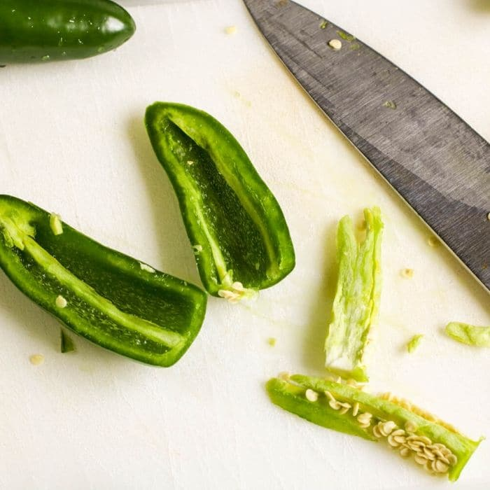 prepping jalapenos on white cutting board
