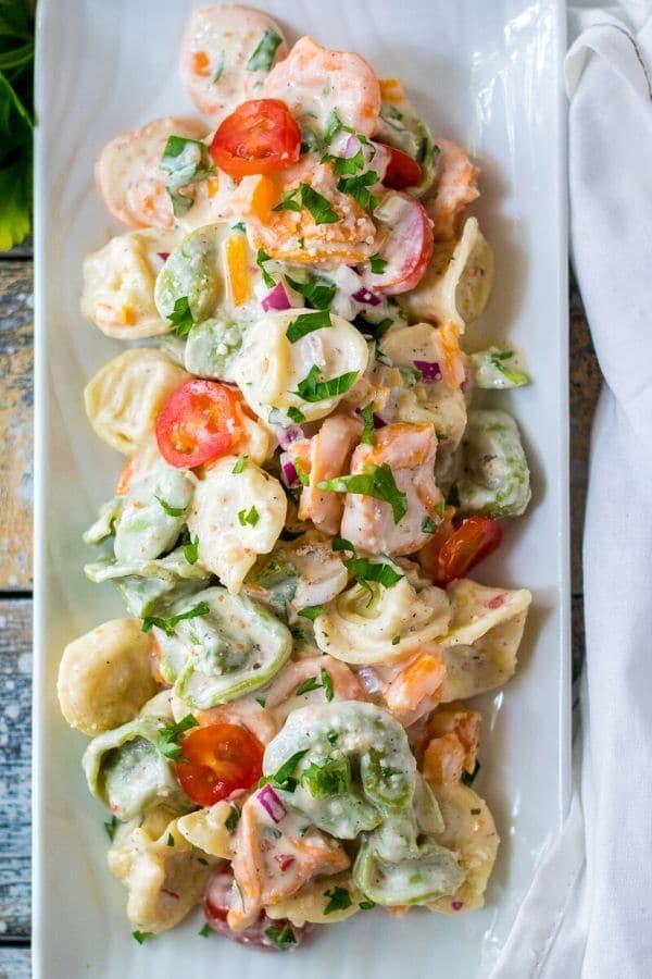 tortellini salad on a rectangle white platter