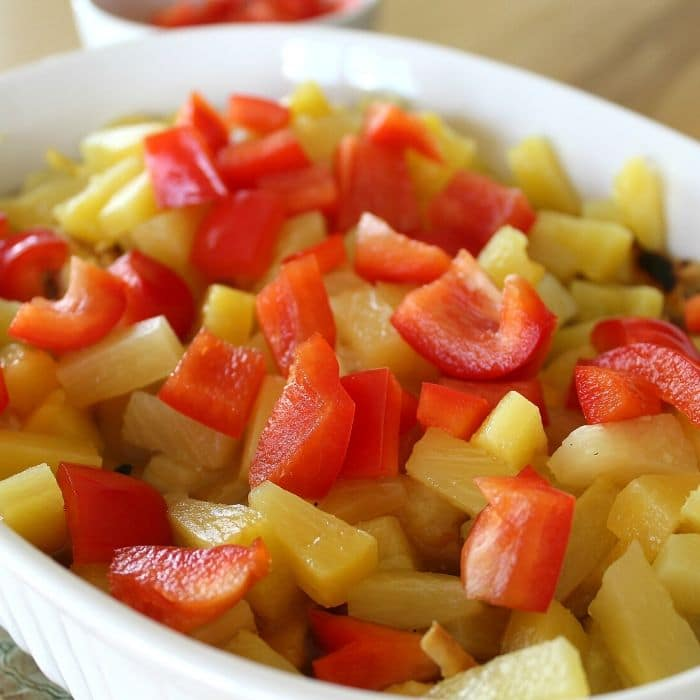 baking dish with pineapple and red peppers on top of chicken