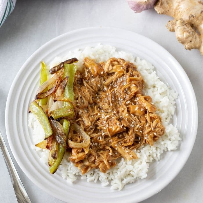 chicken teriyaki on a plate with a bed of rice