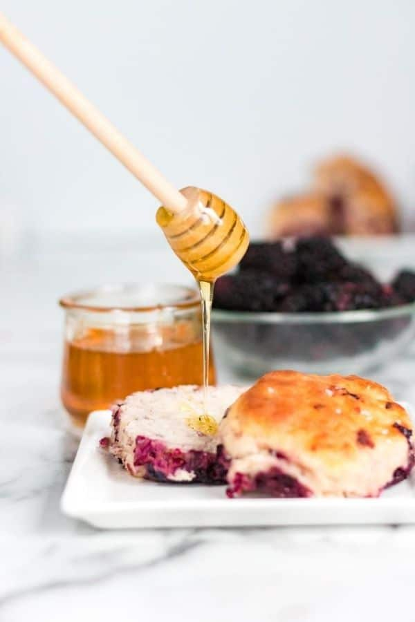 honey being drizzled over blackberry biscuit