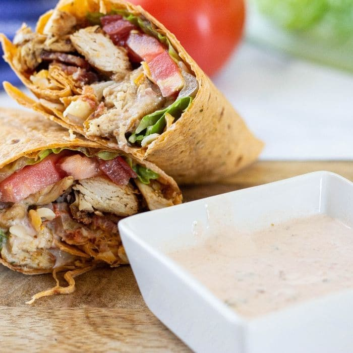 chicken wrap on wooden board with bowl of mexi-ranch
