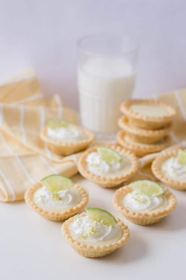 mini key lime pies on a table with glass of milk