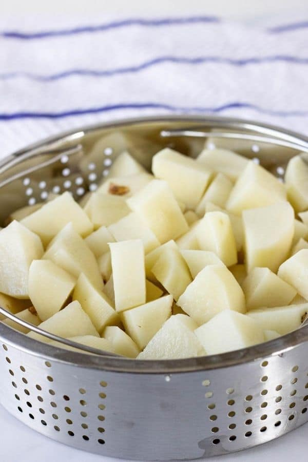 Diced raw potatoes in a steamer basket