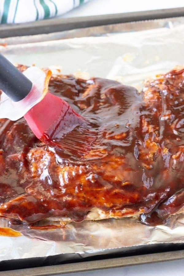 rubbing bbq sauce on pork ribs