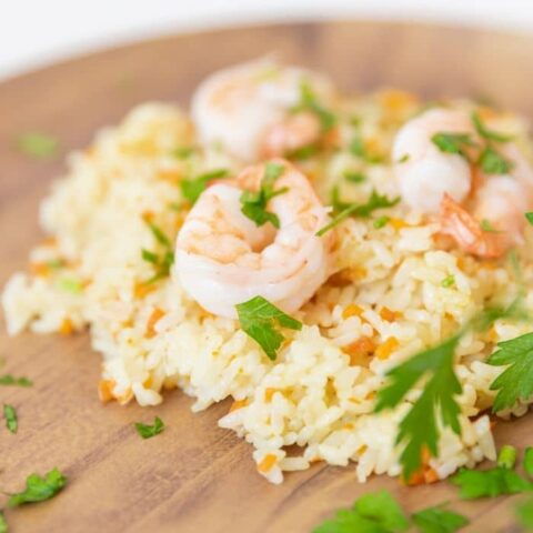 rice pilaf with shrimp on top on a wooden plate
