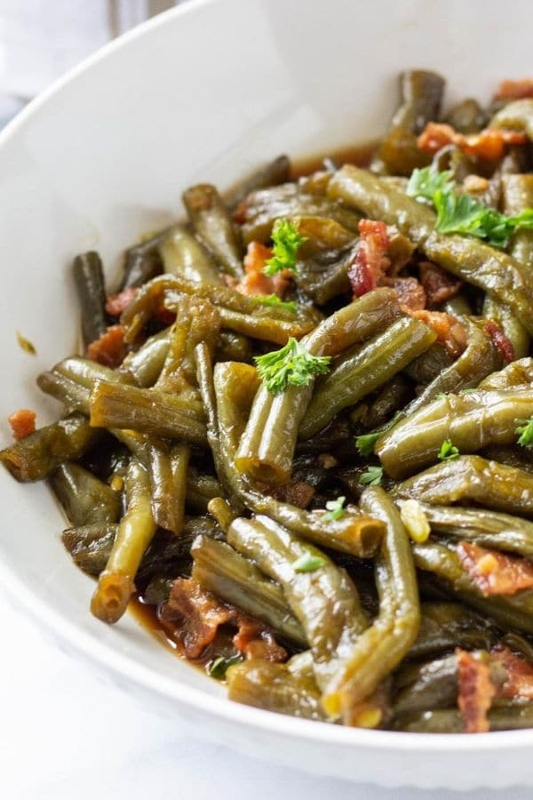 white bowl of green beans and bacon topped with parsley