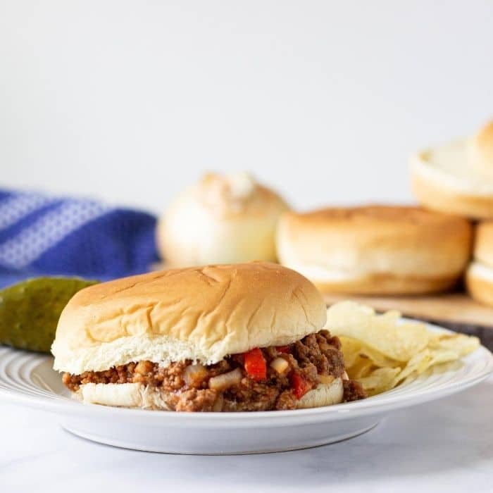 sloppy joe on a plate with chips and a pickle