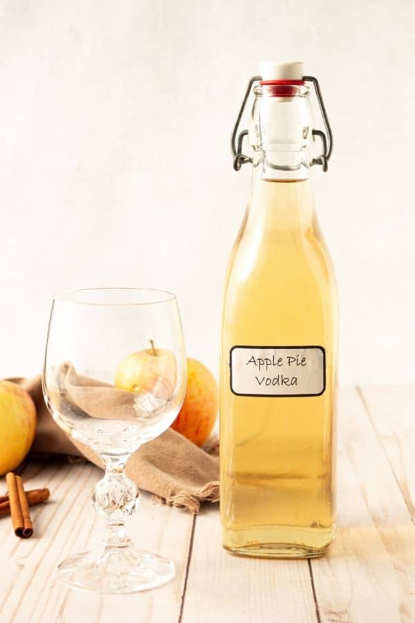 Bottole of apple vodka with wine glass by it