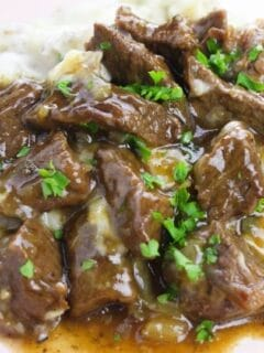 plate of tender beef tips and gravy topped with parsley