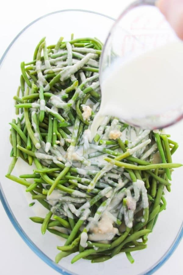 pouring milk into green bean casserole mixture