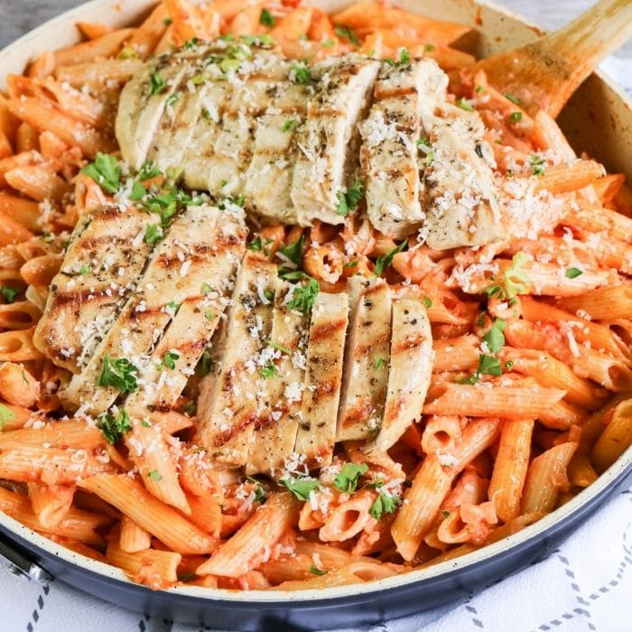Penne Alla Vodka with Chicken in a skillet on table