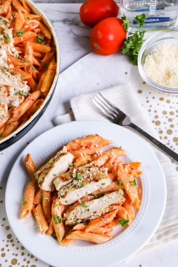 vokda pasta with chicken on a table with items all around it