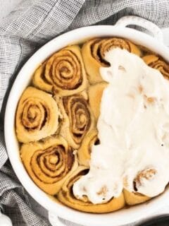 partly frosted pumpkin cinnamon rolls in a pan