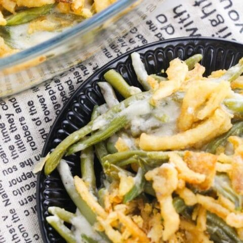 green bean casserole on table with newpaper cloth behind it