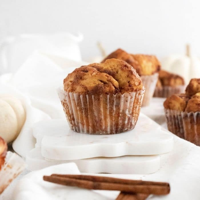 muffin on table with cinnamon sticks by it