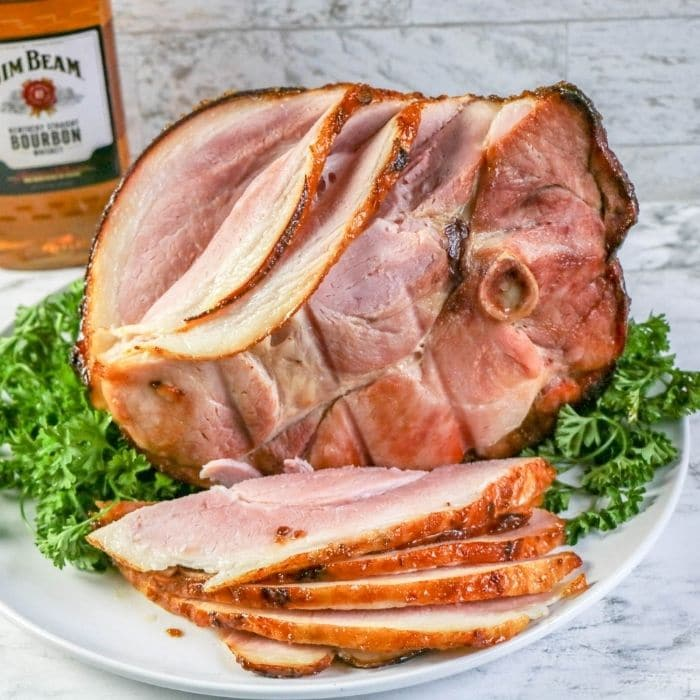 sliced ham on a platter with greens under it