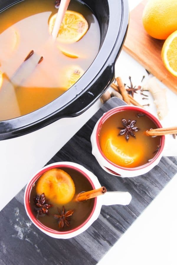 cups of cider and slow cooker with cider in it