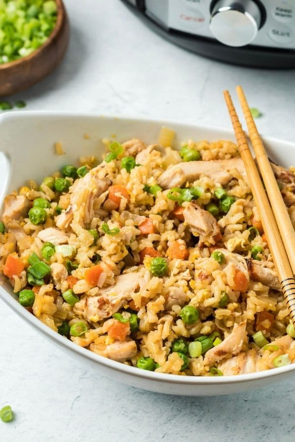 oval bowl of rice and chicken with chopsticks by it