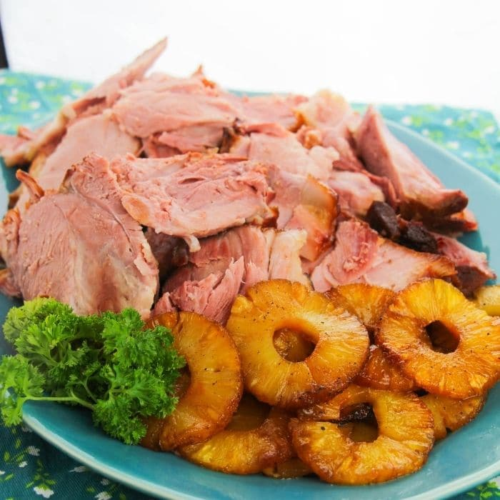 pineapple ham on a platter with pineapples by it