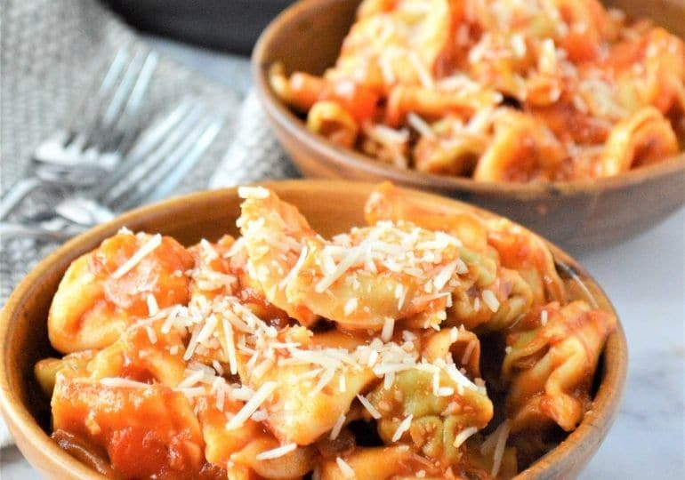 two bowls of pasta with cheese grated on top