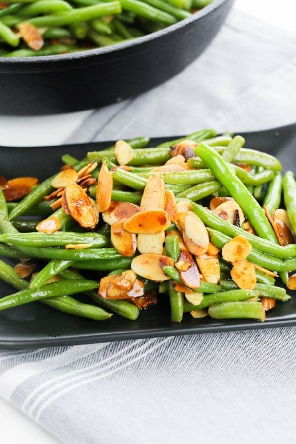 green beans on a plate with pan behind it