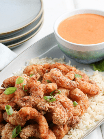 bang bang shrimp on a platter with dipping sauce and plates by it
