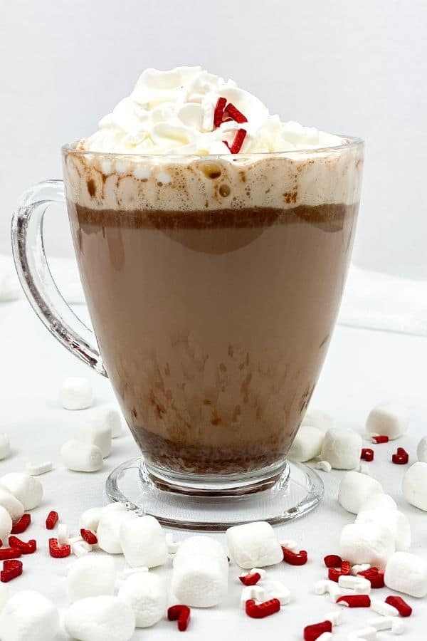 hot chocolate in a clear mug topped with whipped cream