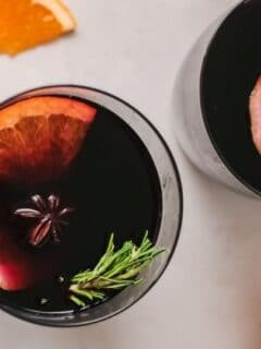 mulled wine in cups with oranges on a table
