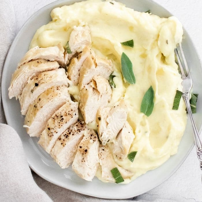 potatoes and chicken on a plate with sage on top