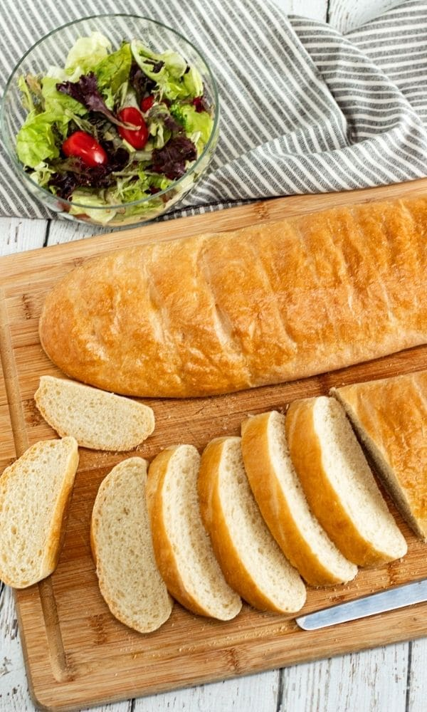 artisan bread on cutting board with salad behind it