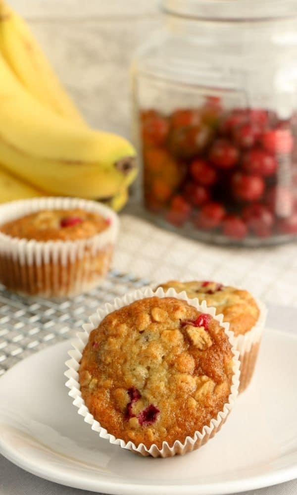 cranberry muffins on plate with bananas behind it