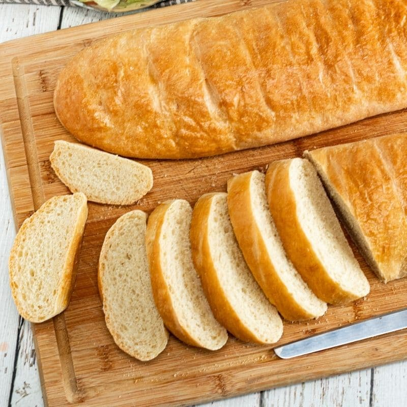 two french breads on a wood cutting board on table